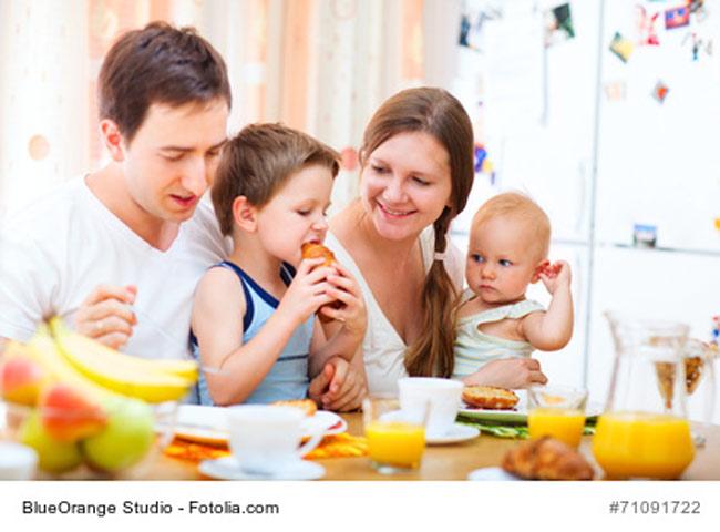 Familie isst mit Baby