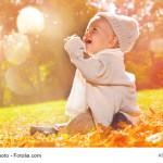 Sitzendes Baby mit Mütze